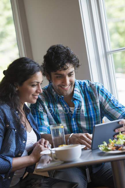 Paar Blick auf eine digitale tablet — Stockfoto