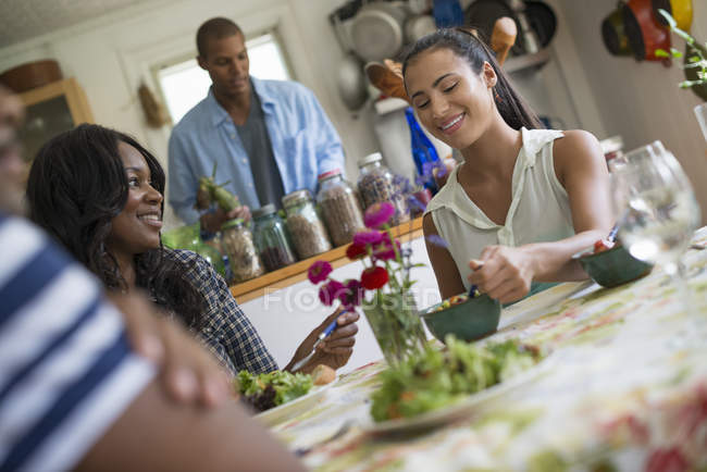 Group of friends at a meal in a farmhouse kitchen. — Stock Photo