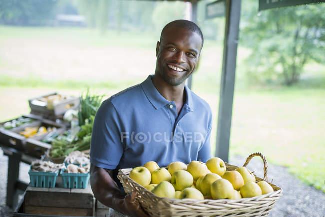 Hombre que lleva manzanas . - foto de stock