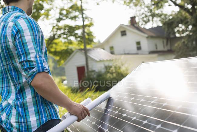 Человек с панелью солнечных батарей — стоковое фото