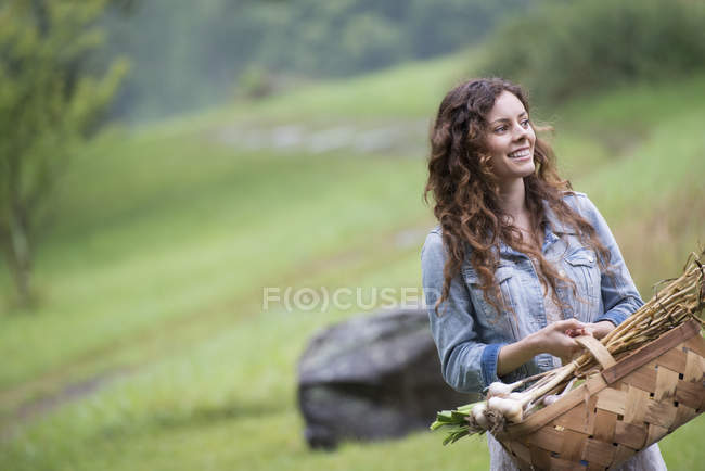 Woman carrying basket of garlic and vegetables — Stock Photo