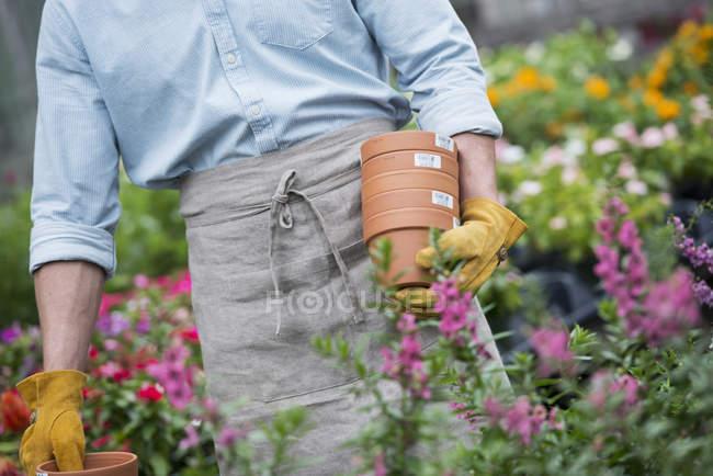 Homem carregando vasos para plantas. — Fotografia de Stock