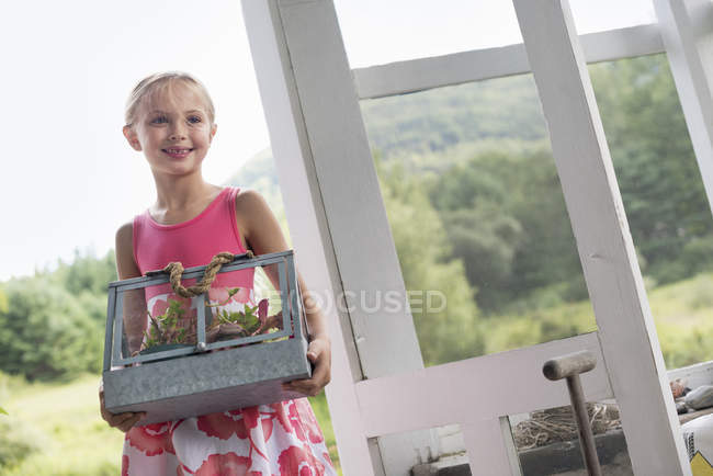 Girl with terarium containing small plants. — Stock Photo