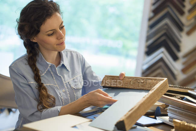 Woman choosing frames and cardboard mounts — Stock Photo