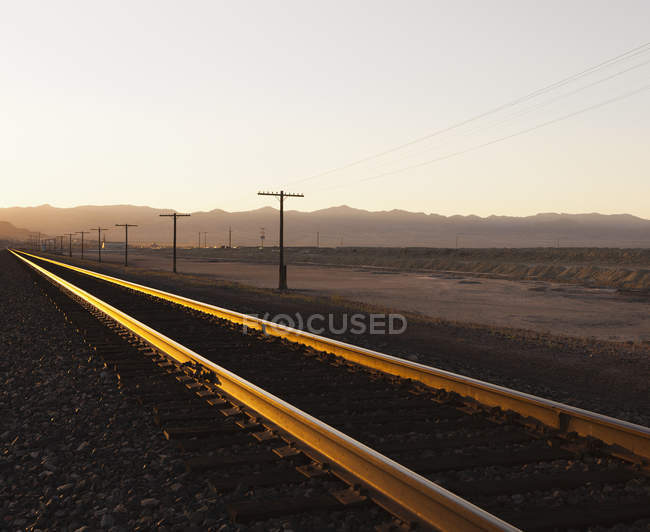 Railroad tracks extending across desert — Stock Photo