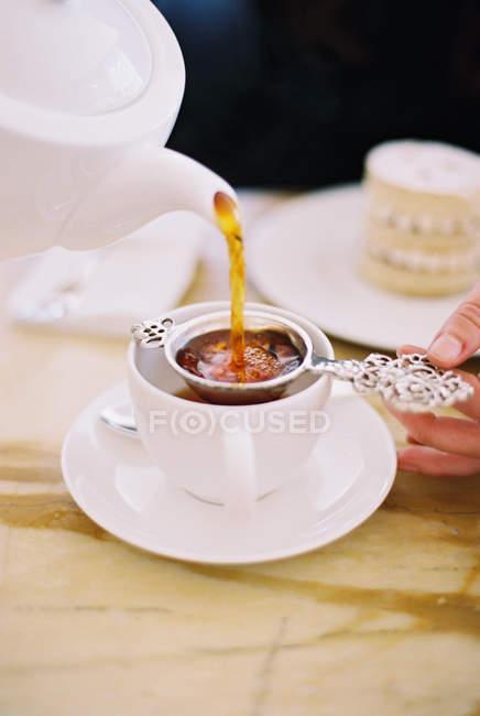 Personne de verser une tasse de thé — Photo de stock