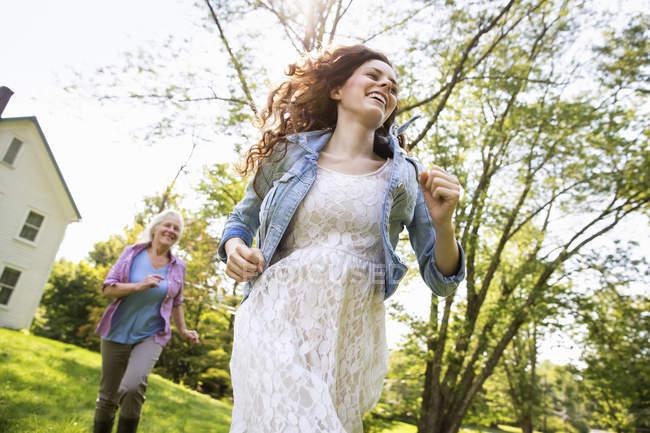Donne che corrono nel cortile vicino alla casa — Foto stock