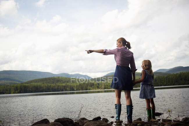 Woman and a child looking over water. — Stock Photo