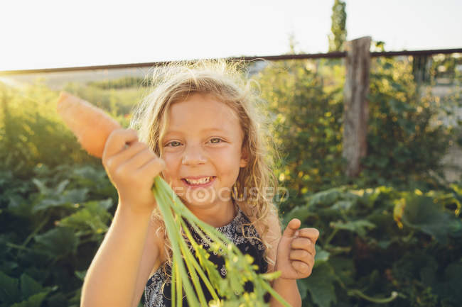 Girl  holding fresh picked carrot — Stock Photo