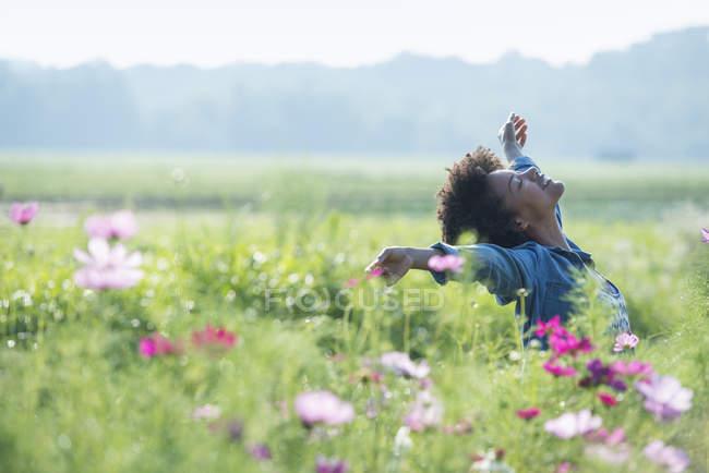 Mulher de pé entre flores — Fotografia de Stock