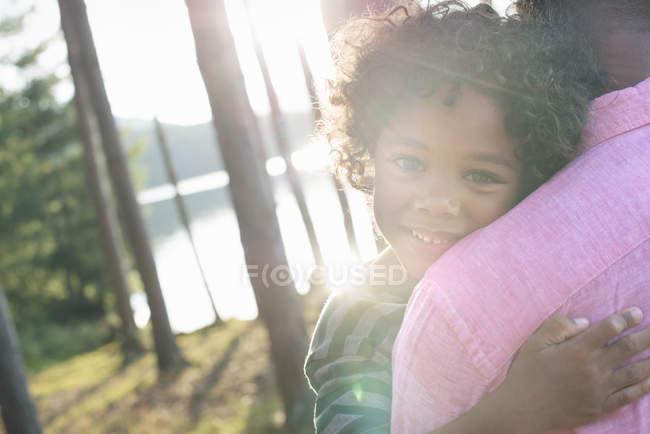 Homme portant un enfant dans les bras — Photo de stock