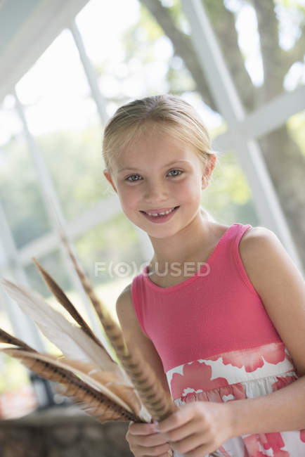 Girl with bunch of bird feathers. — Stock Photo