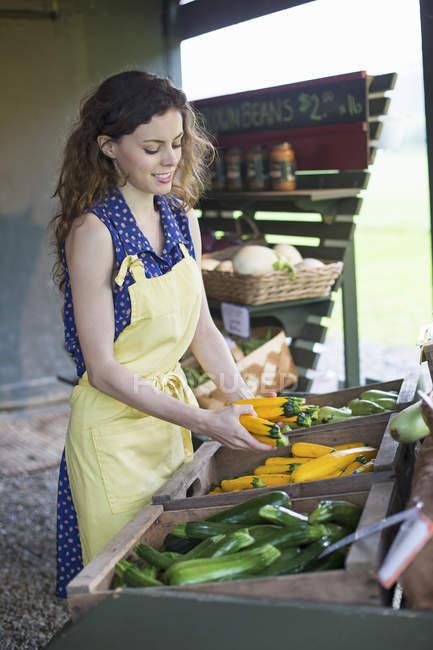Молода жінка сортування овочі. — стокове фото