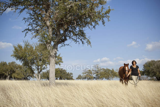 Woman leading horse — Stock Photo