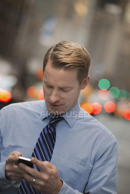 Hombre con teléfono celular en una calle concurrida - foto de stock