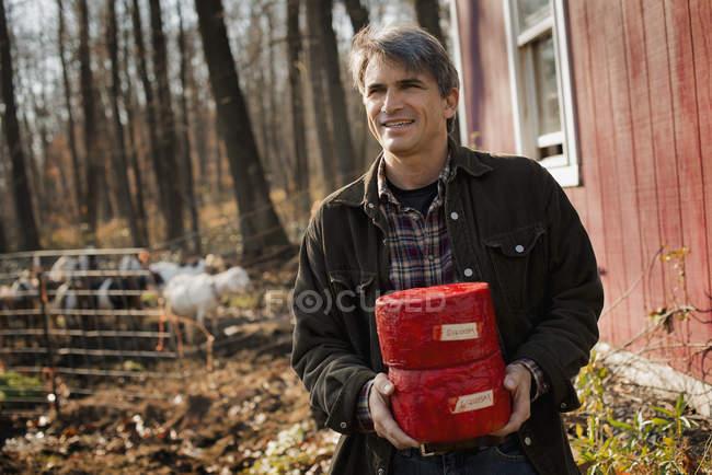 Homem segurando blocos de queijo de cabra — Fotografia de Stock
