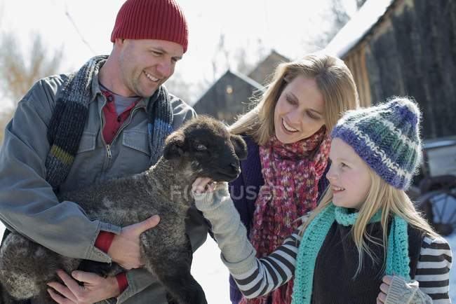 Family holding a young lamb — Stock Photo