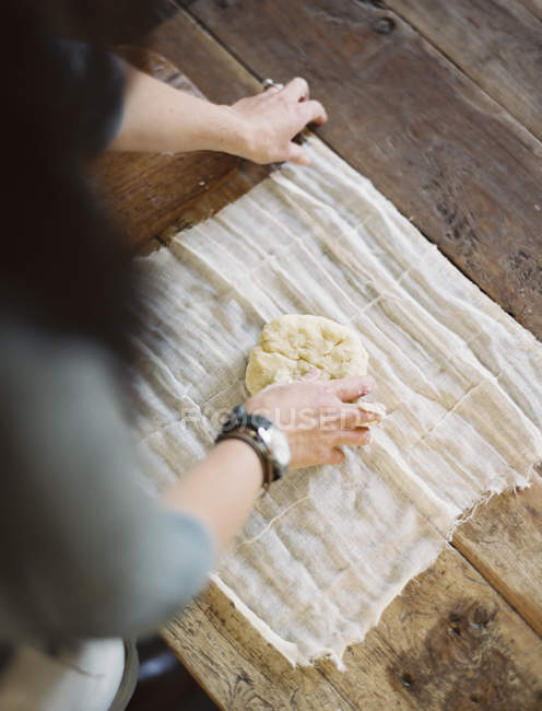Woman wrapping fresh pastry — Stock Photo