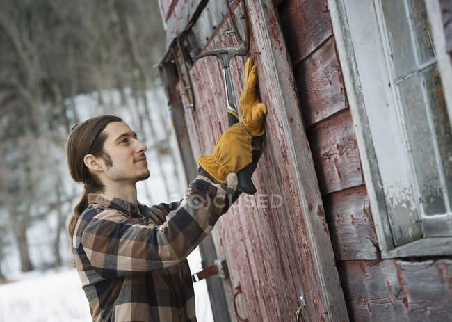 Man mending barn door. — Stock Photo
