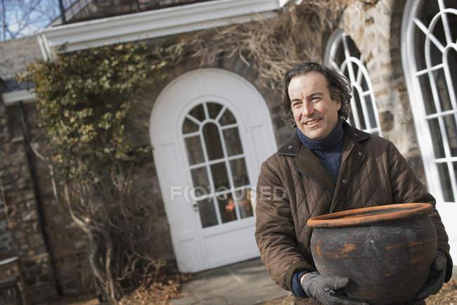 Uomo che trasporta grande vaso di terracotta — Foto stock