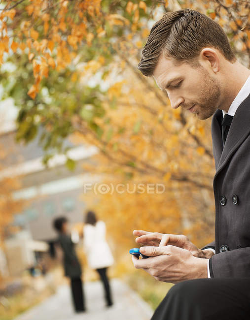 Man in the park checking mobile phone. — Stock Photo