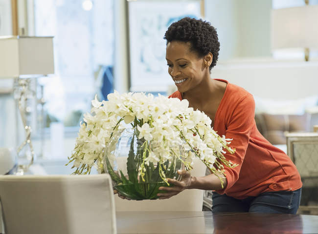 Woman placing vase of flowers — Stock Photo