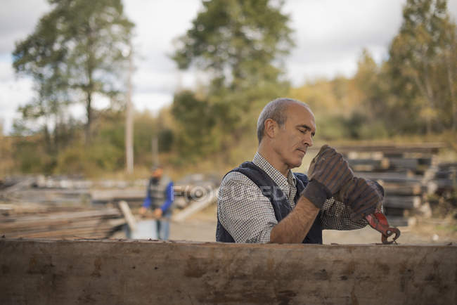 Men working in a reclaimed timber yard. — Stock Photo