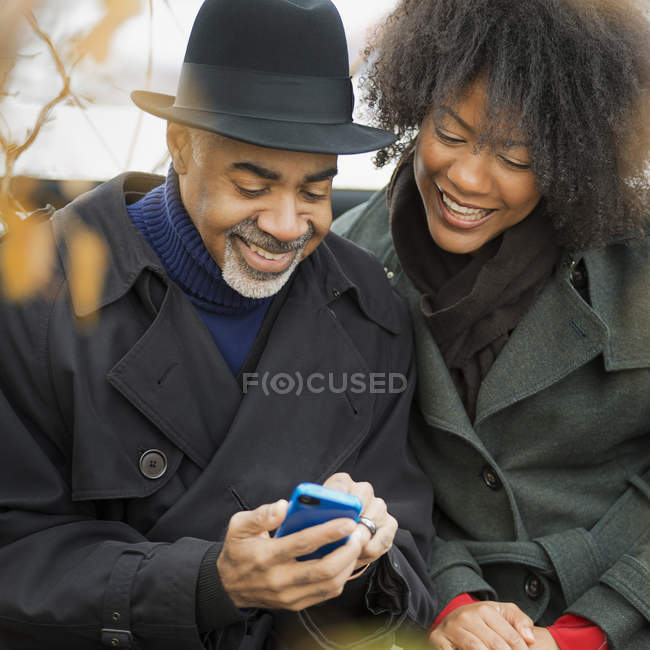 People side by side with mobile phone — Stock Photo
