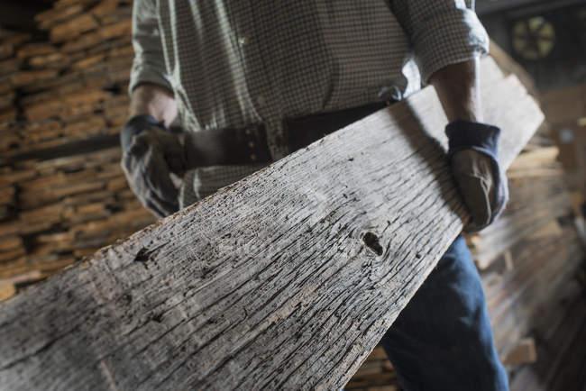 Hombre llevando gran tablón de madera - foto de stock