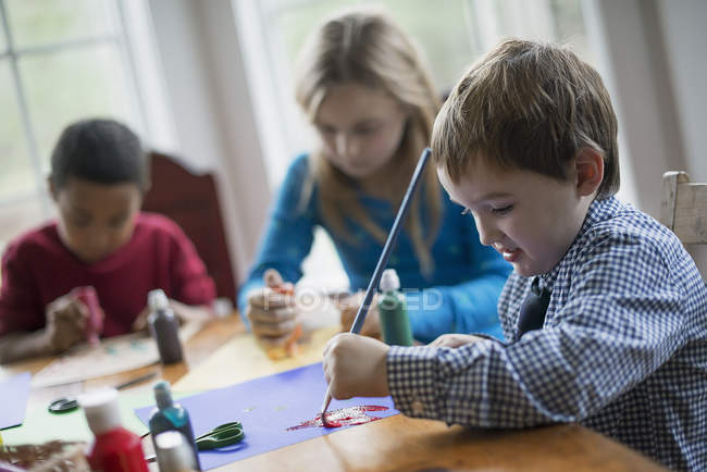 Children using paint to create decorations. — Stock Photo