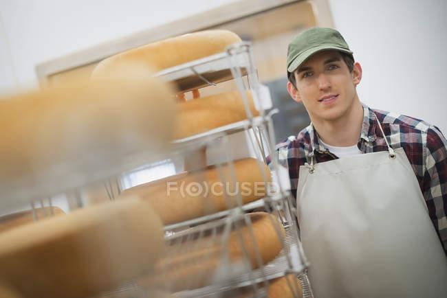 Uomo con grandi ruote di maturazione del formaggio — Foto stock
