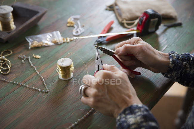 Female Hands twisting wire on necklace — Stock Photo