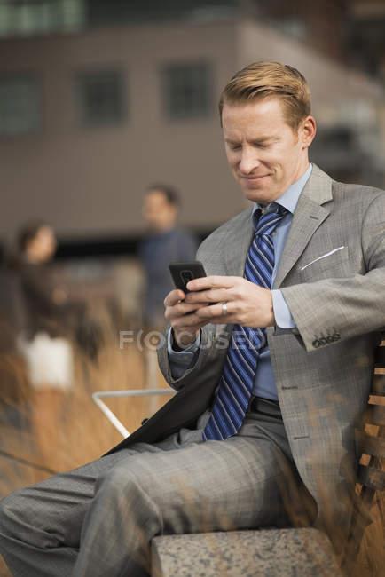 Бизнесмен смотрит на мобильный телефон — стоковое фото