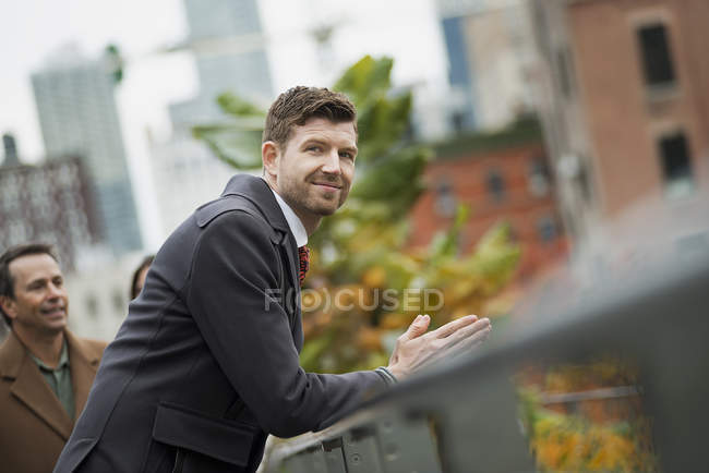 Man in a winter coat leaning on a railing — Stock Photo