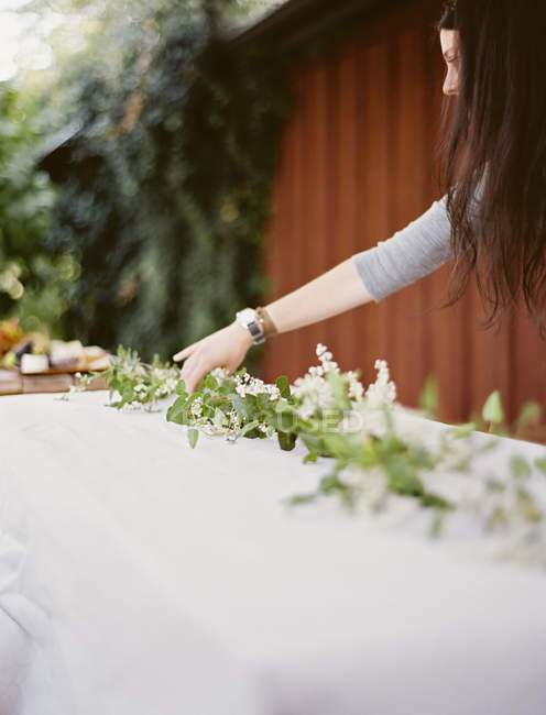 Woman decorating table with foliage — Stock Photo