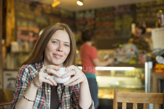 Woman sitting in coffee shop and cafe — Stock Photo