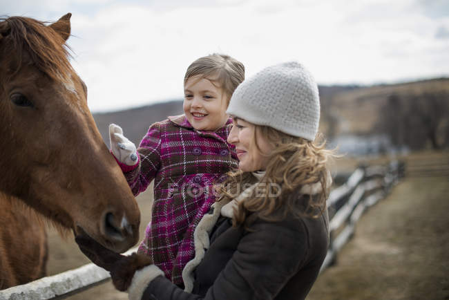 Woman and girl patting horse — Stock Photo