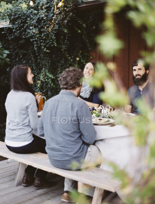 People around a table in a garden. — Stock Photo
