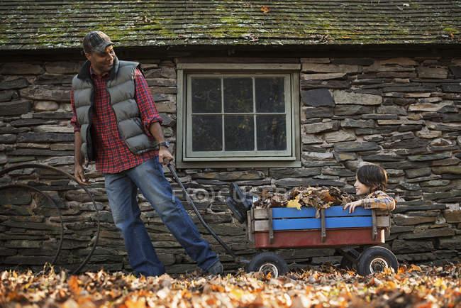 Homem puxando um carrinho de jardim com uma criança — Fotografia de Stock