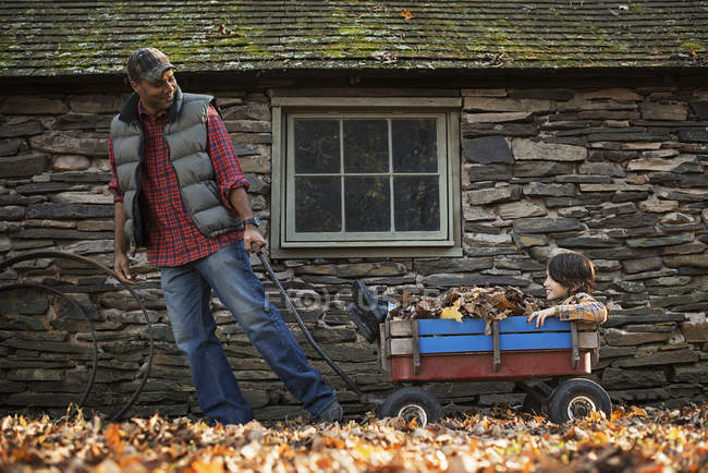 Hombre tirando de un carro de jardín con un niño - foto de stock