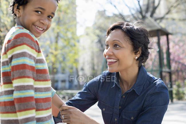 Мать, преклоняющая колени перед сыном — стоковое фото