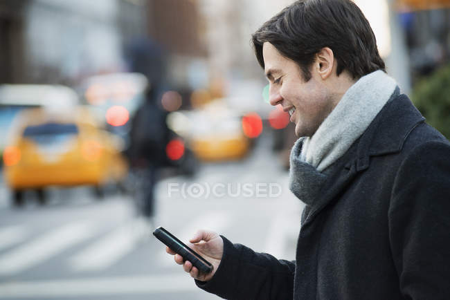 Man with smartphone on busy street — Stock Photo