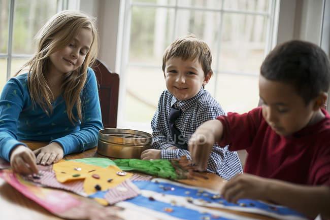 Three children creating pictures — Stock Photo
