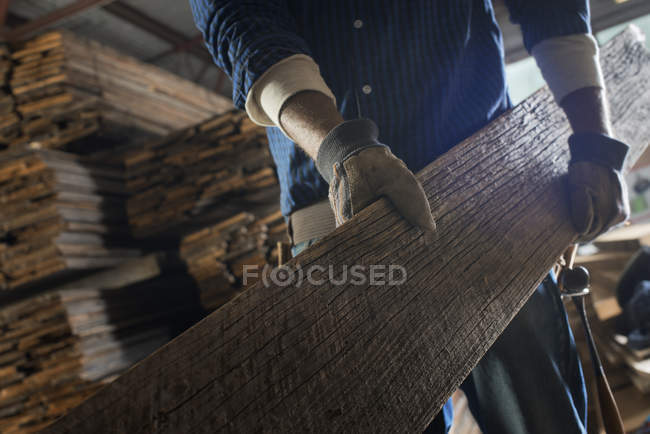 Man carrying large plank of wood — Stock Photo