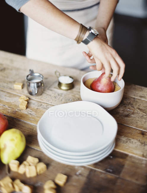 Dipping fresh organic pears into a sauce — Stock Photo