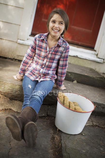 Chica con un gran cubo de hierro y guantes . - foto de stock