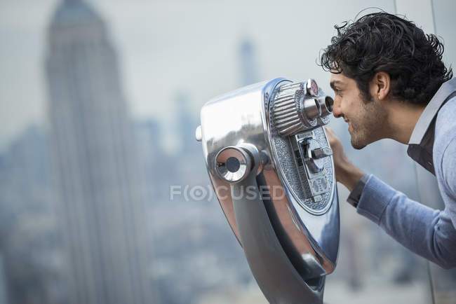 Man looking through a telescope over the city. — Stock Photo