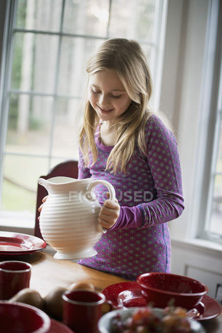 Girl holding a white pottery jug. — Stock Photo