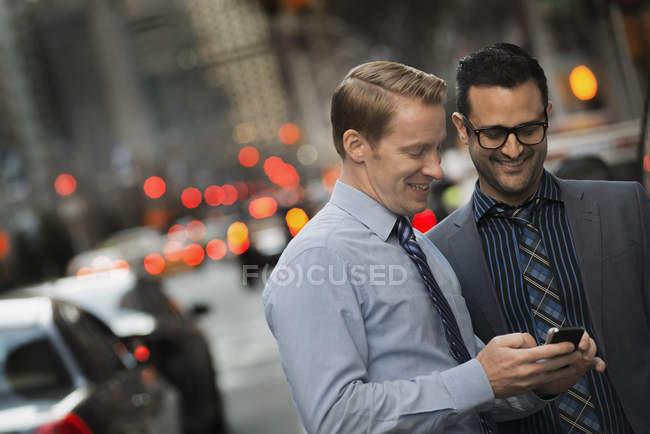 Uomini con cellulare in una strada trafficata — Foto stock