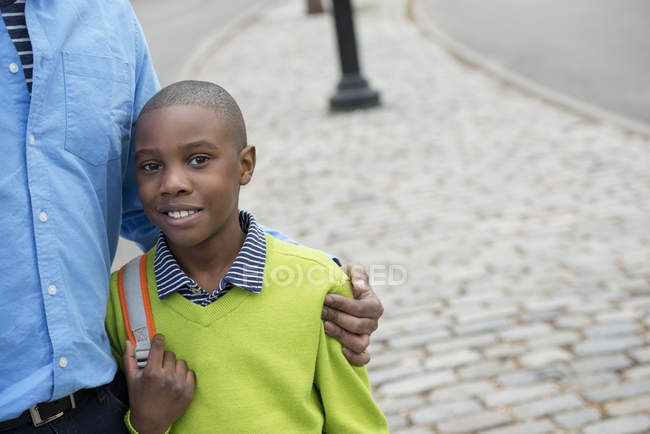 Boy holding bag, beside his father — Stock Photo